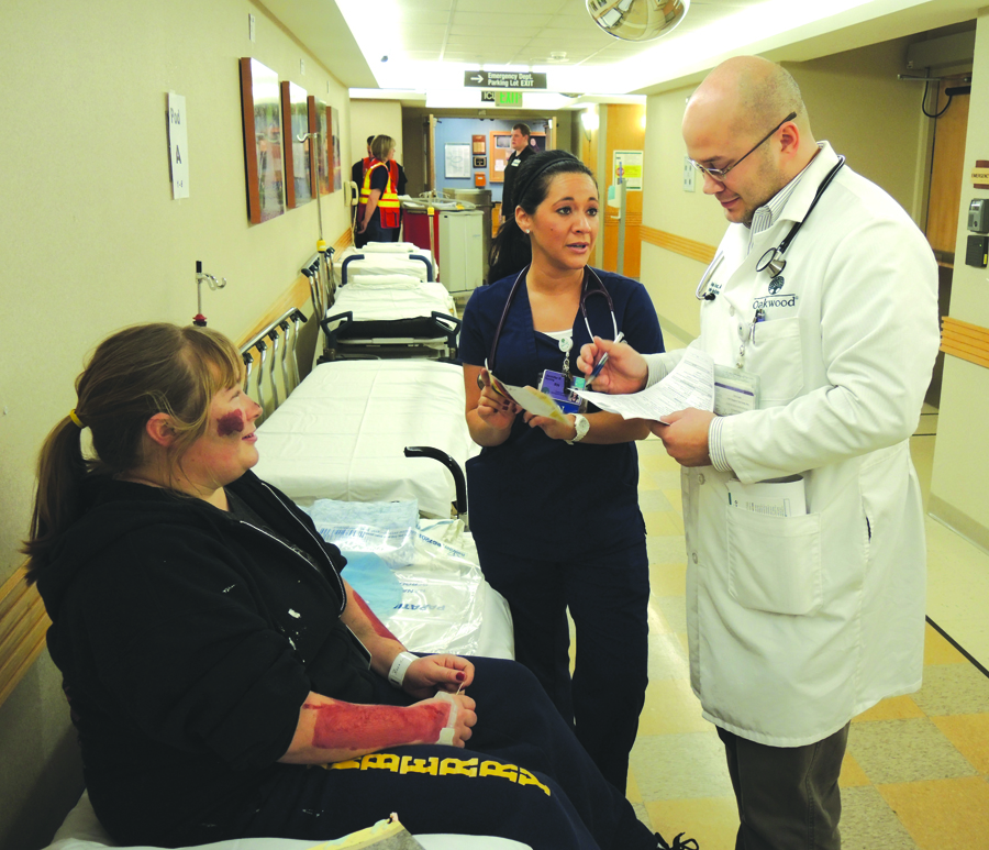 Douglas Grucz, MD, and Jennifer Rivera, RN, evaluate mock patient RoseAnn Dubke during a tornado response drill at Oakwood Annapolis Hospital on Wednesday. About 60 volunteer 'victims' were treated during the exercise, which was designed to test the hospital's ability to respond to a large scale community emergency.