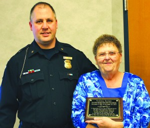 Wayne Police Chief Jason Wright presents Pat Dawson with a plaque to honor her 27 years of service as a crossing guard.