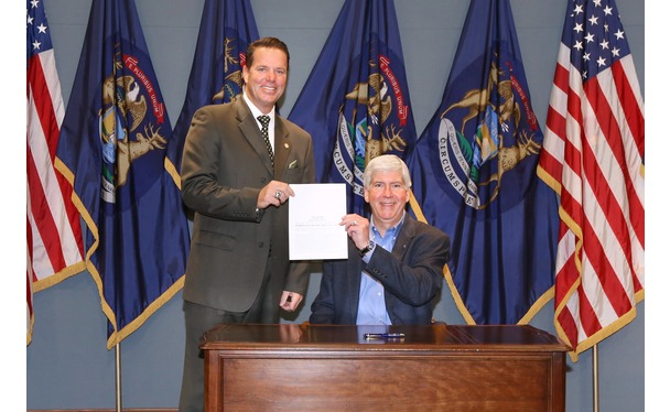 Governor Snyder signs for the Delphi Worker Compensation Package bill with State Representative Robert Kosowski.