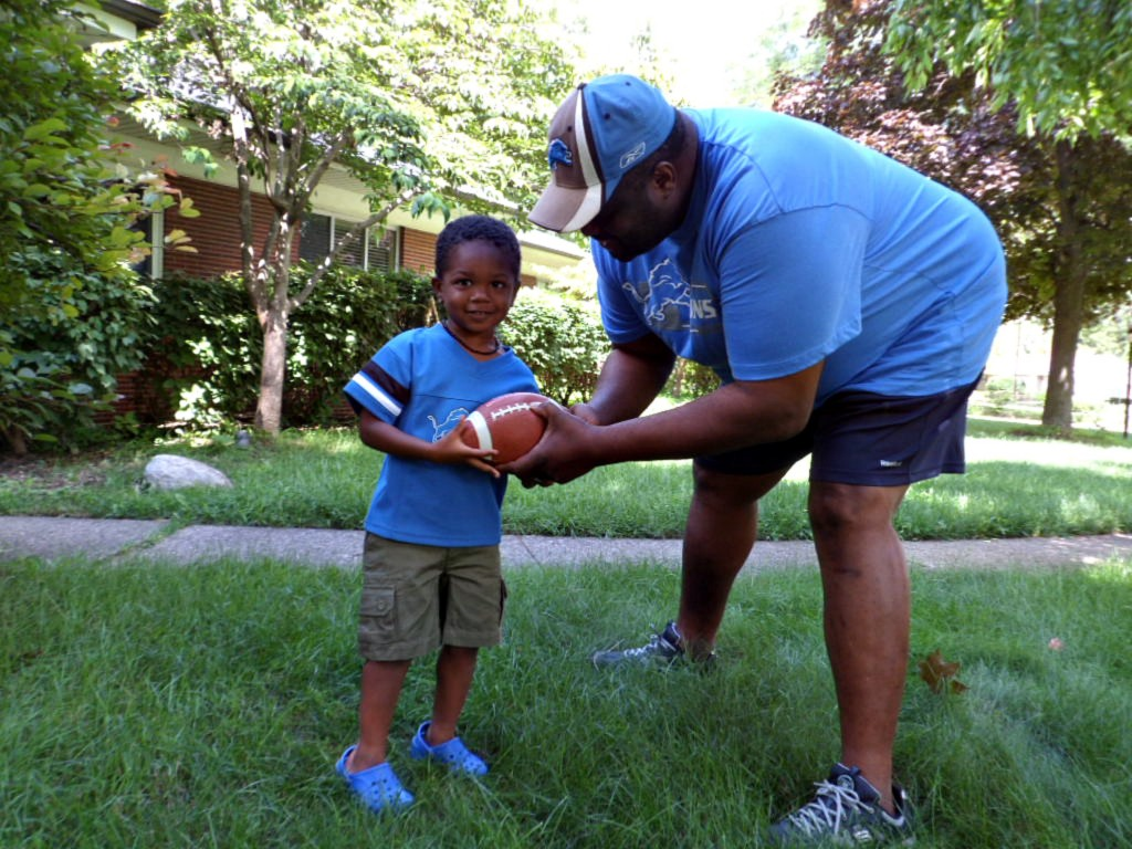 Scotty Jr., age 3, learns the fundamentals of football from his dad.