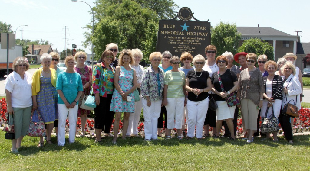 Members of the Wayne Garden Club stand in front of the new Blue Star Memorial Highway marker on Michigan Avenue in the median in front of Harry J. Will Funeral Home. Photo by John P. Rhaesa