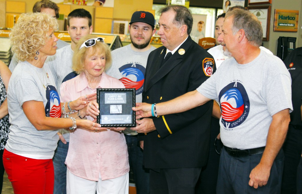 Cathy Buchanan, Frances Francavilla, owner, and Robert Francavilla receive a piece to the World Trade Center from retired New York Battalion Chief Ed Breen. Photo by John P. Rhaesa