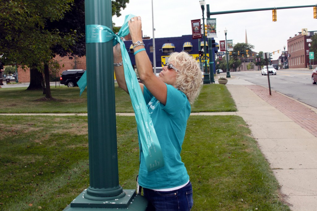 Cathy Buchanan ties ribbons on downtown poles for National Ovarian Cancer Awareness Month.