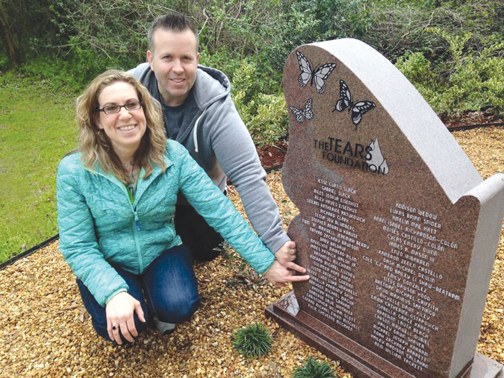 Allen (Buddy) and Shelby Shuh point to their 5 1/2 month old daughter, Isabella Harmony Shuh's name on the Tears monument.
