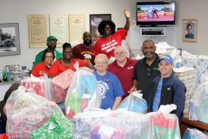 Santa's UAW helpers Patty Martin (Co-Chair),  Mike Smith (Vice President), Anderson Robinson Jr. (President),  Bill Johnson Jr. (Financial Secretary). Back, Danita Brantley (Editor), Ulysses Edmonson,  Ebony Kennedy (Chair), Fernando Merida (District Committee) and Judy Reynolds (Secretary) show off some of the gifts being donated to people in the community.